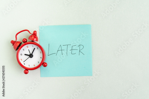 Fotomural Procrastination, postpone or laziness concept, red alarm clock on sticky note wi