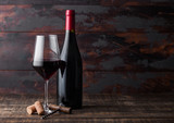 Elegant glass and bottle of red wine with corks and corkscrew on dark wooden background. Natural Light