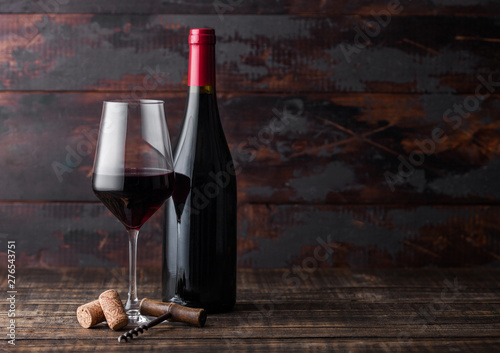 Papiers peints Vin Elegant glass and bottle of red wine with corks and corkscrew on dark wooden background. Natural Light
