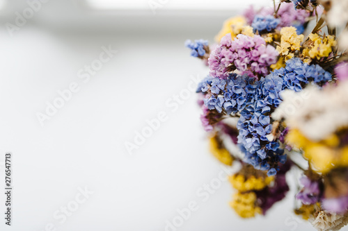 Foto auf AluDibond Blumen Composition dried colored flowers standing on a white background of the table. copy space. Romantic flowers. Place for text and design. Greeting card. Flat lay, top view.