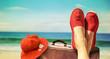 canvas print picture Beine mit roten Stoffschuhen vor Strand und Meer
