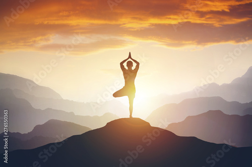 Photographie Man meditating on high mountain in sunset background