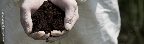 panoramic shot of ecologist in latex gloves holding handful of soil Canvas-taulu