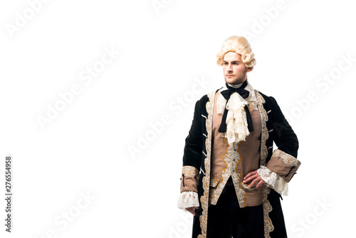 Photo handsome victorian man in wig standing with hand on hip isolated on white