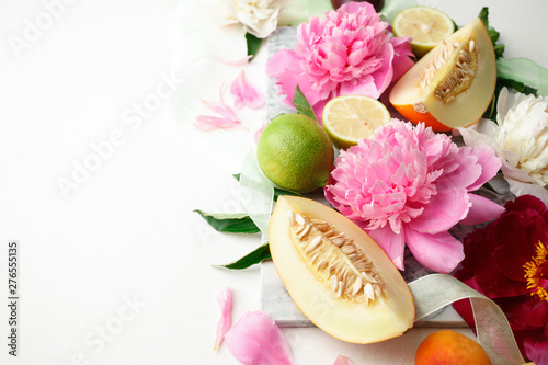 Still life with fresh assorted exotic fruits and peony flowers on white background. Concept of healthy eating with fruits and seasonal flowers. Wedding decor - 276555135