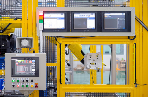 Factory 4.0 concept : View of operation panel and product inspection monitoring display on fence of manufacturing machine.