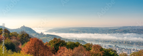Poster Piscine Panoramic view of the hill Drachenfels with the castle ruin, the castle Drachenburg in Siebengebirge and the town Königswinter, morning fog arose from the river Rhine valley, NRW, Germany