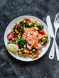 Warm chickpeas, cherry tomatoes, spinach, roasted salmon salad - healthy lunch on a dark background, top view