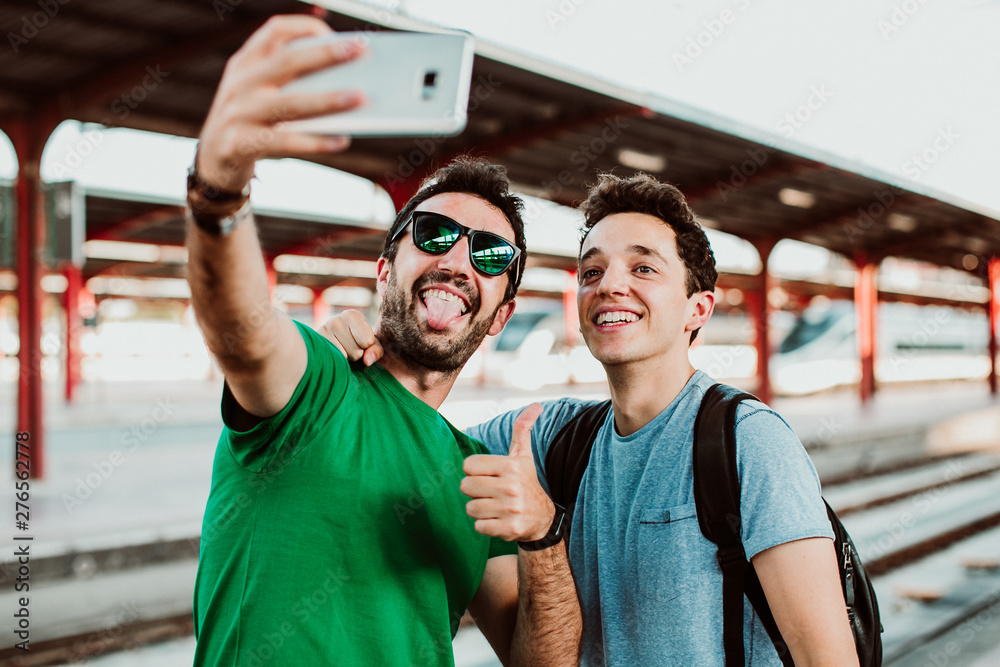 Fototapety, obrazy: .Two brothers on the platform waiting for the train to start their summer vacation. Taking pictures together with their cellphone. Lifestyle. Travel photography