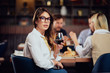 Portrait of gorgeous brunette looking at camera and holding glass with red wine while sitting at restaurat. In background friends eating diner.