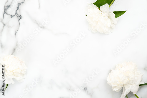 Foto auf AluDibond Blumen Top view frame of white peony flowers on marble background. Minimal flat lay style home desk with peonies. Wedding invitation card mockup with copy space. Beauty or fashion blog banner template