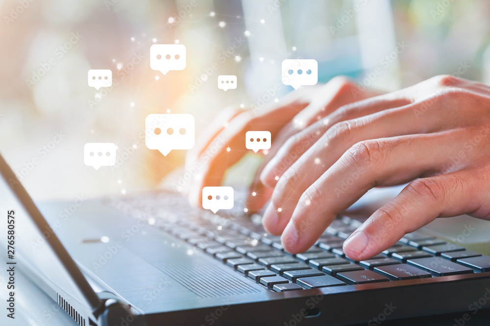Fototapeta Live chat chatting and social network concepts, Close-up hands typing on keyboard laptop with chat box icons