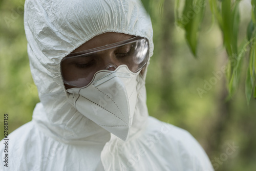 Valokuvatapetti ecologist in protective costume, goggles and respirator looking down