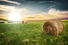 Idyllic Farm Field With Hay Bales On On The Background Of The Picturesque Sky At Sunset.