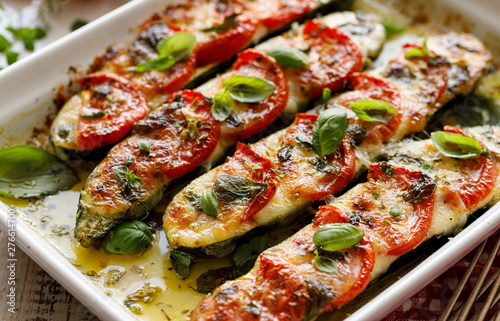 Roasted zucchini with the addition of tomatoes, mozzarella cheese, fresh basil and olive oil (caprese salad) in a ceramic baking dish, close-up. Nutritious and tasty vegetarian dish