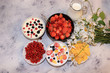 Strawberry yogurt, milk and ripe berries of currants and strawberries on a light background.