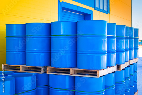 Blue containers loaded on pallets. Plastic barrels for toxic products. Chemical storage tanks. Barrels for shipment from stock. Transport of hazardous substances. Warehouse work. Logistics in stock.