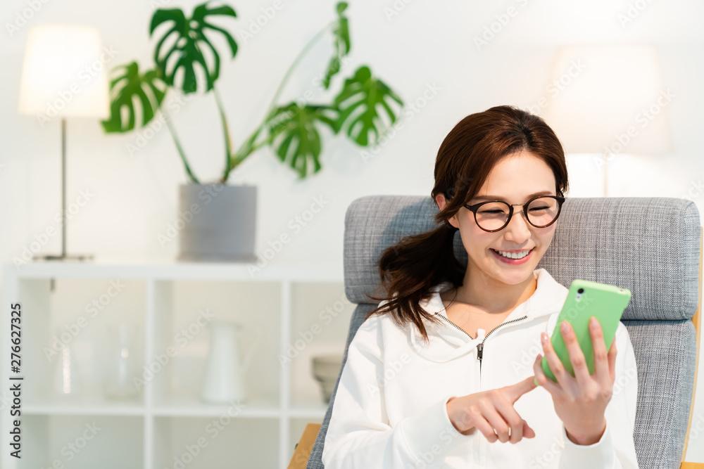 Fototapeta 部屋でスマホを見る女性