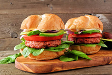Plant Based Meatless Burgers With Avocado, Tomato And Spinach On A Serving Board Against A Rustic Wood Background