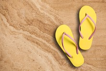 Yellow Rubber Sandals Flip Flops On Wooden Background