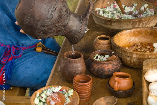 Fototapeta A woman pours water from a clay jug into a stein while sitting at a wooden table in nature. obraz