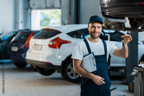 happy bearded car mechanic looking at camera and holding clipboard and key near cars