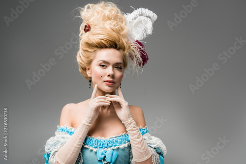 Fotografia beautiful victorian woman in wig with feathers looking at camera and touching fa