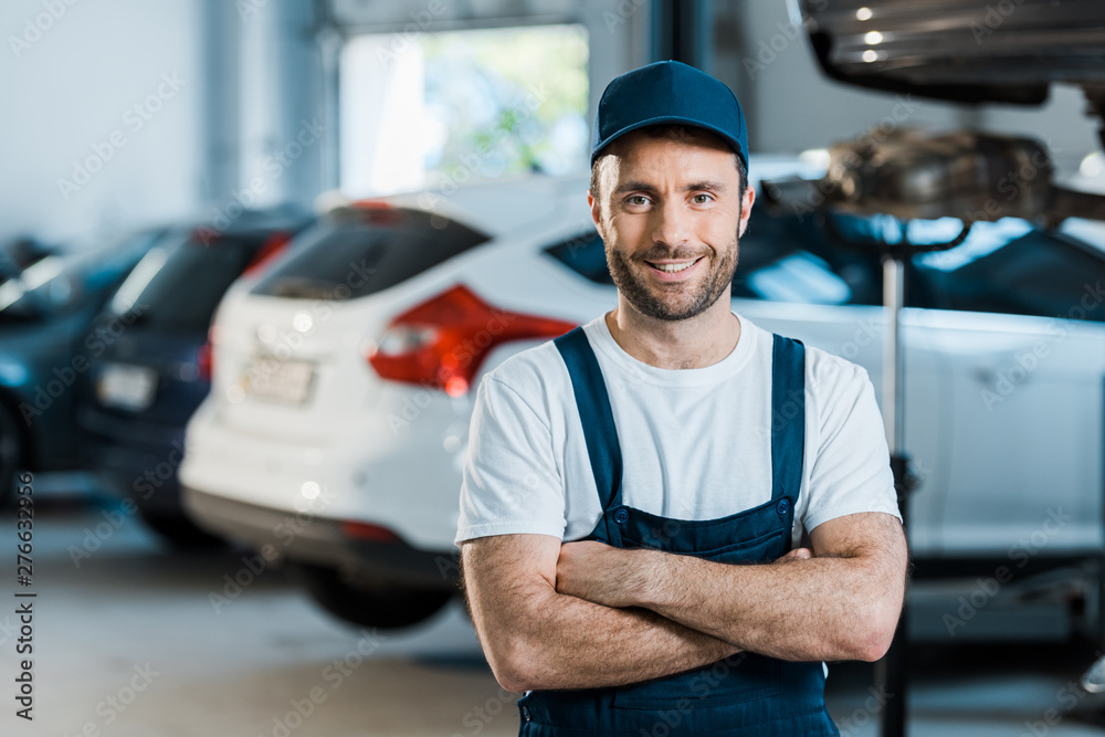 Fototapety, obrazy: happy car mechanic standing with crossed arms in car service