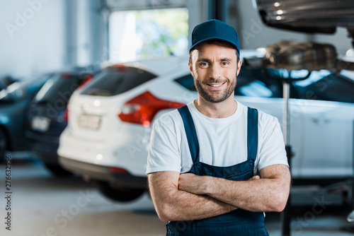 plakat happy car mechanic standing with crossed arms in car service