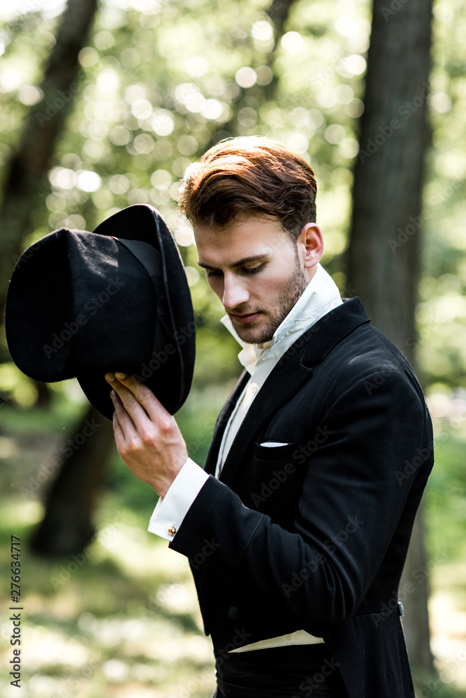 Fototapety, obrazy: handsome aristocratic man holding hat while standing in suit