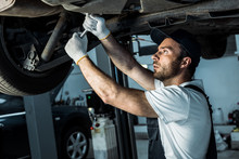 Bearded Auto Mechanic In Cap Repairing Automobile In Car Service