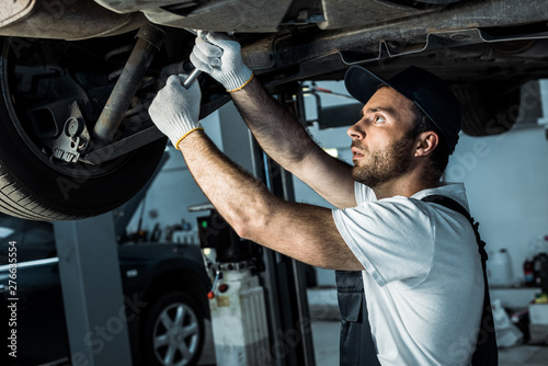 Valokuva  bearded auto mechanic in cap repairing automobile in car service