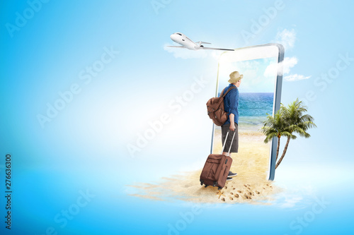 Rear view of asian man in hat with suitcase bag and backpack walking to the beach