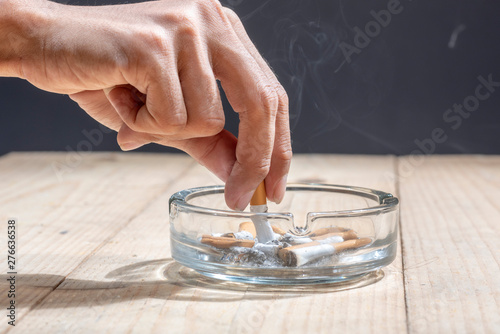 Photo Hand stubbed out cigarette in a transparent ashtray