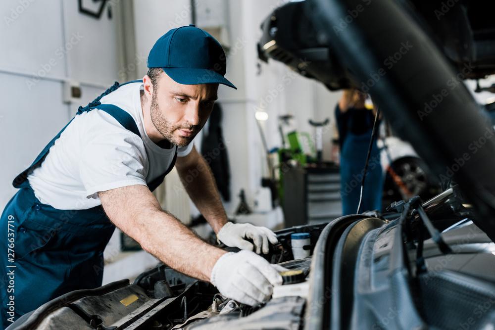 Fototapeta selective focus of bearded car mechanic in gloves fixing automobile