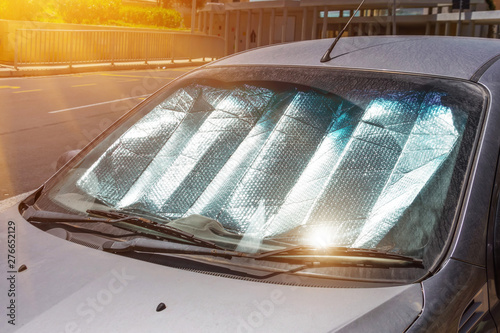 Protective reflective surface under the windshield of the passenger car parked on a hot day, heated by the sun's rays inside the car. - 276652129
