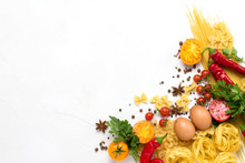 Different Types Of Italian Pasta, Nests, Spaghetti, Spices, Red Hot Chilli Pepper, Chicken Eggs, Tomatoes, Cherry, Light White Stone Background. Flat Lay, Top View