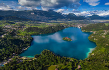 Bled, Slovenia - Aerial Panoramic Skyline View Of Lake Bled (Blejsko Jezero) From High Above With The Pilgrimage Church Of The Assumption Of Maria, Bled Castle And Julian Alps At Background At Summer