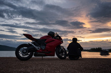 Young Biker Sitting On Side Of Sport Big Bike With Sightseeing At Sunset