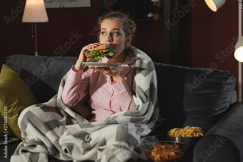 Fototapeta Beautiful young woman eating unhealthy food at night obraz