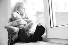 Homeless Little Girl Sitting On Window Sill