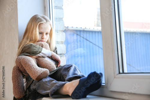 Homeless little girl with teddy bear sitting on window sill Fototapete