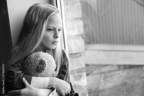 Vászonkép  Homeless little girl with teddy bear sitting on window sill