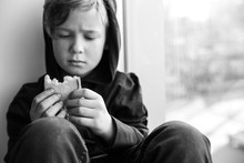 Homeless Little Boy With Bread Sitting On Window Sill Indoors