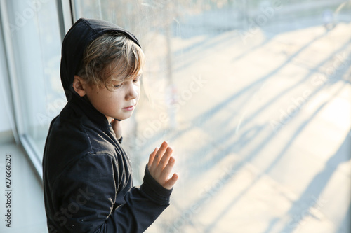 Foto Homeless little boy near window indoors