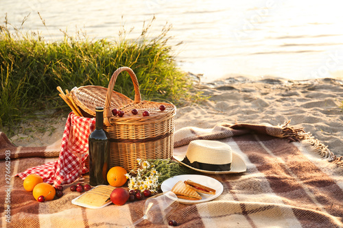 Obraz na plátně Wicker basket with tasty food and drink for romantic picnic near river
