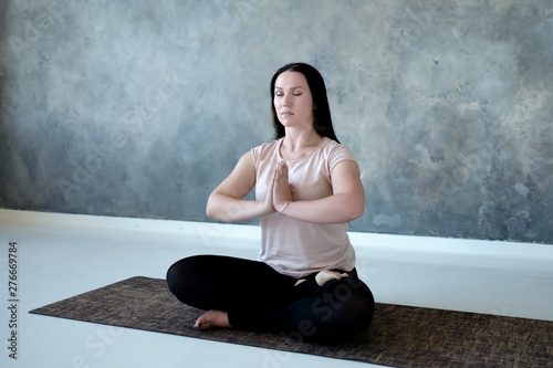 Poster Individuel Young caucasian woman meditating on the floor on gray background