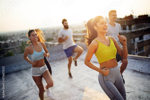 Poster de jardin Route Group of happy fit friends exercising outdoor in city
