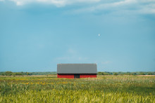 View Of Barn In Field Against Blue Sky