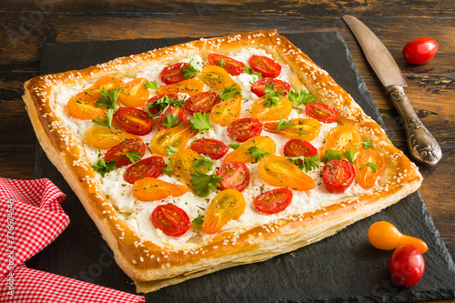Fotografía Puff pastry cake with ricotta and cherry tomatoes on wooden rustic table